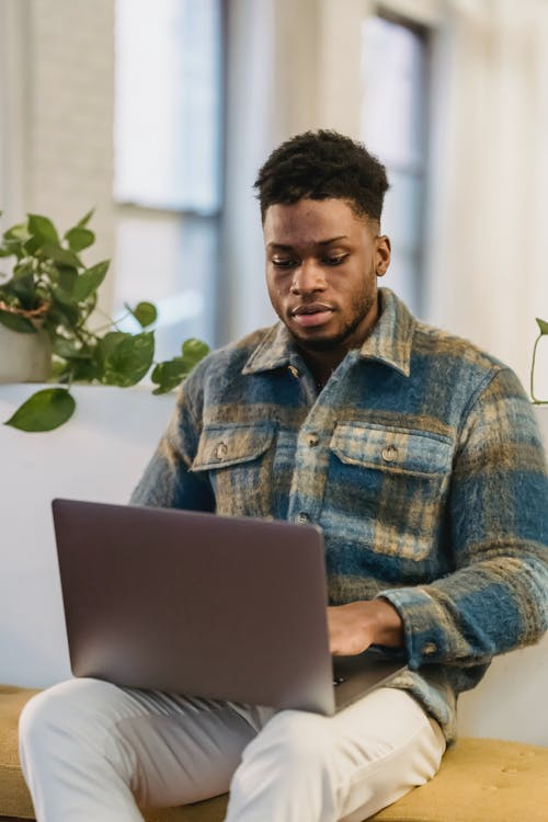 Serious young bearded black male freelancer in checkered shirt working distantly on laptop at home