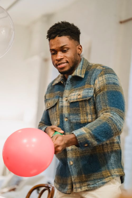 Happy young black man blowing balloon with pump at home