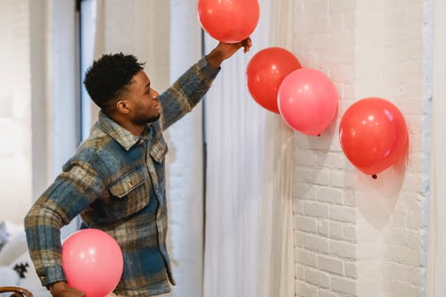 Cheerful African American man with balloons