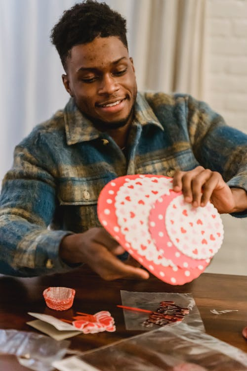 Smiling bearded black male in shirt looking down while sitting at wooden table and holding decorations for Saint Valentine day