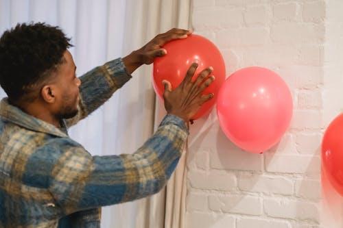 Black man sticking balloons to brick wall