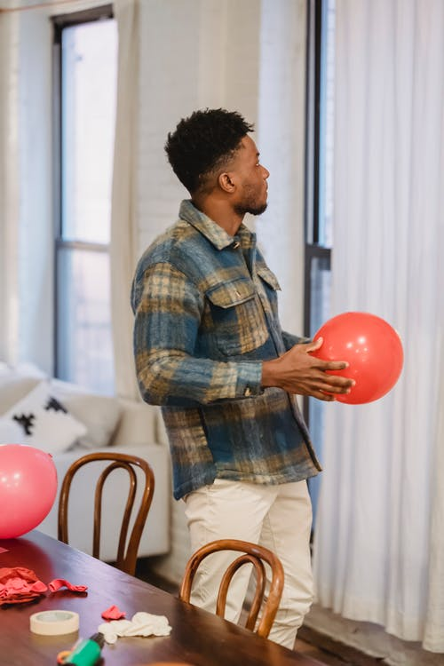 African American man standing with red balloon