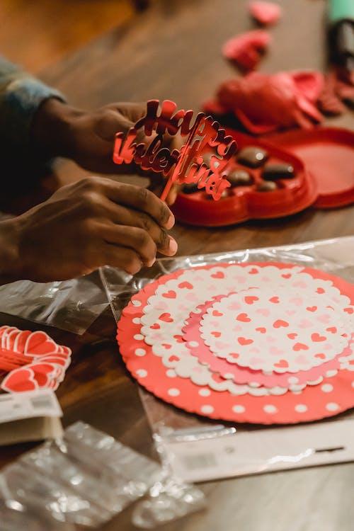 Black man making decorations for Saint Valentine Day