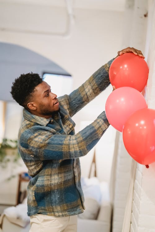 Side view of young bearded African American male in casual clothes standing near white wall and decorating room with inflatable balloons