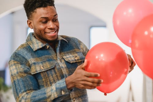 Smiling black man holding red balloon