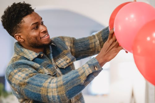Bearded black man in checkered shirt correcting red balloons position while decorating room to special event