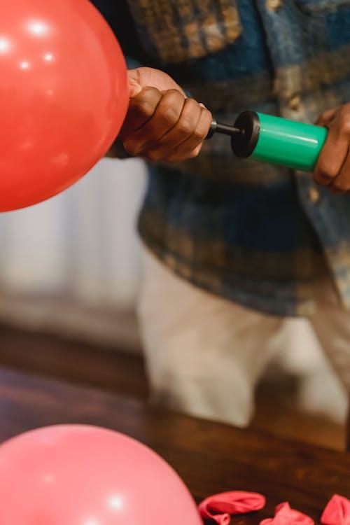 Black man inflating balloon with pump