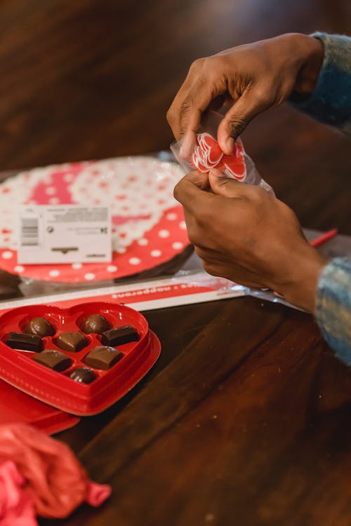 Crop faceless black male sitting at wooden table with delicious red box of sweets in shape of heart and holding small paper hearts