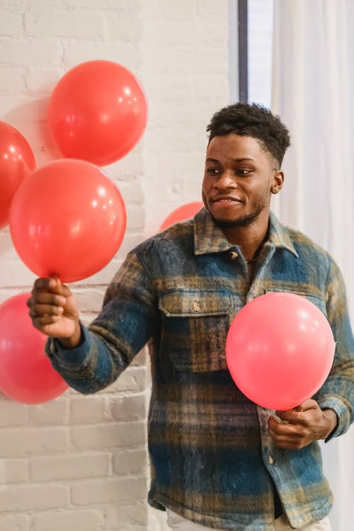 African American man holding red balloons