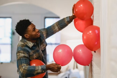 Positive black guy decorating wall with colorful balloons