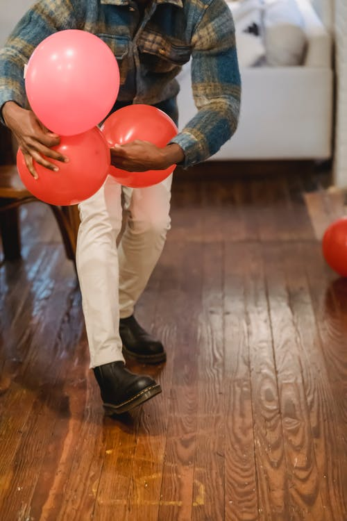 Busy black man carrying red balloons