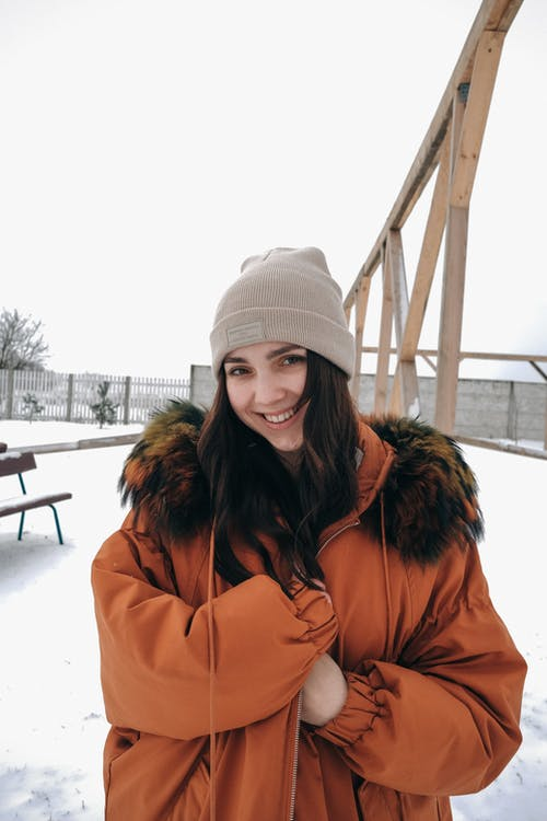 Happy young woman wearing warm jacket and hat while standing on snowy meadow under bright sky near wooden constructions in winter day and looking at camera