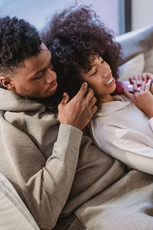 From above of crop loving African American boyfriend touching hair of ethnic happy girlfriend