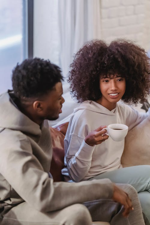 From above of cheerful African American couple talking with each other while resting at home