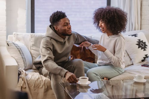 Positive African American couple talking and laughing on comfortable sofa at home in daytime