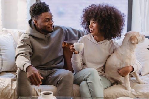 Joyful black couple with dog and coffee on sofa