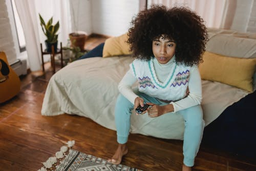 From above of concentrated young African American female with dark curly hair in casual outfit watching TV with interest while resting on sofa at home