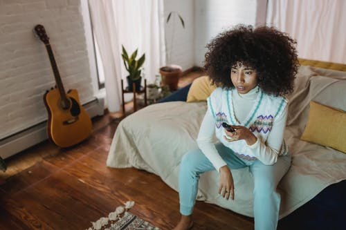 Calm young ethnic woman watching TV sitting on couch during weekend at home