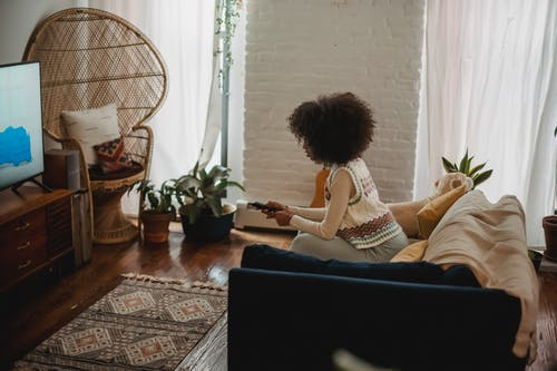 Focused young ethnic woman with remote controller watching TV at home