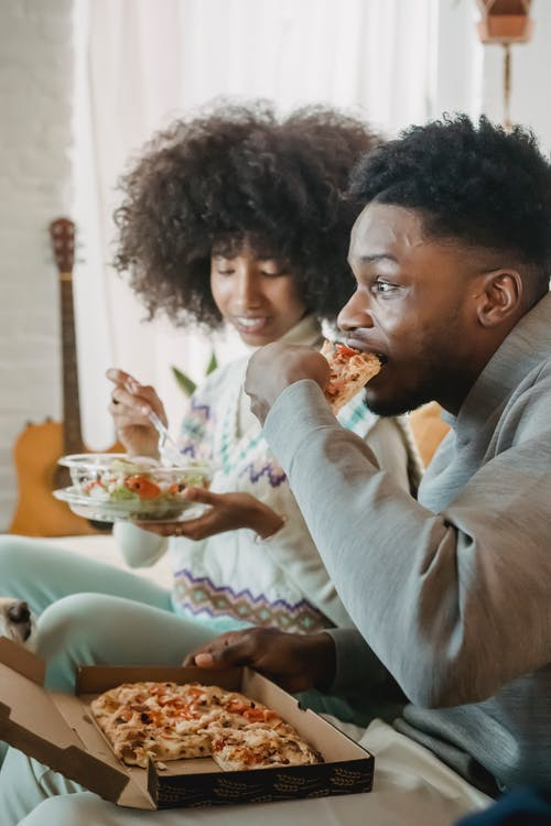 Surprised African American crop male eating pizza while ethnic girlfriend having snack with salad
