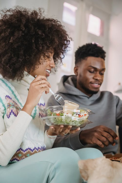 Glad black couple eating and talking at home