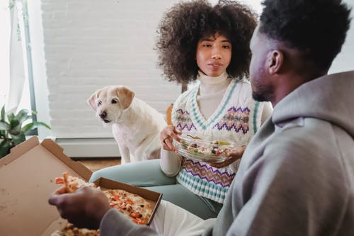 Crop African American couple speaking with each other while having snack with pizza and salad at home with hungry dog