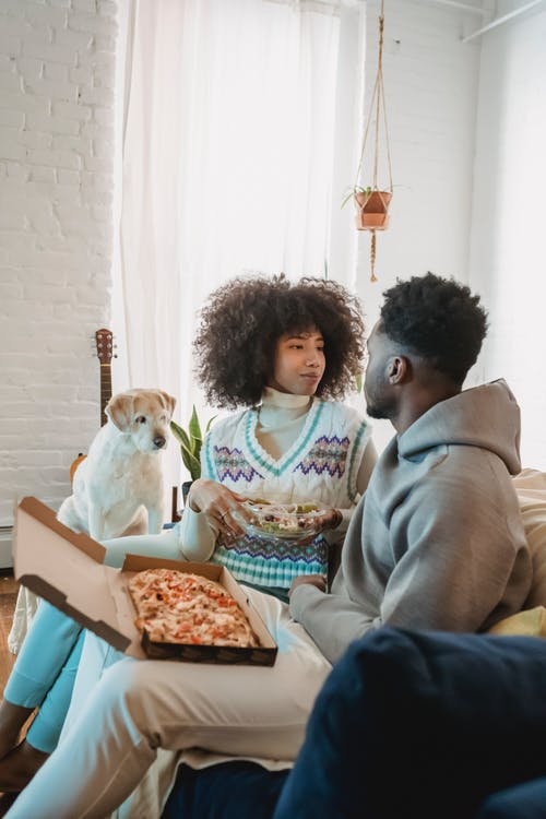 Romantic African American couple looking at each other while enjoying pizza and salad near cute dog at home