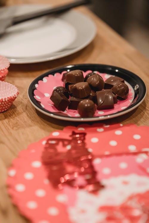 Homemade chocolate sweets on plate near festive cake