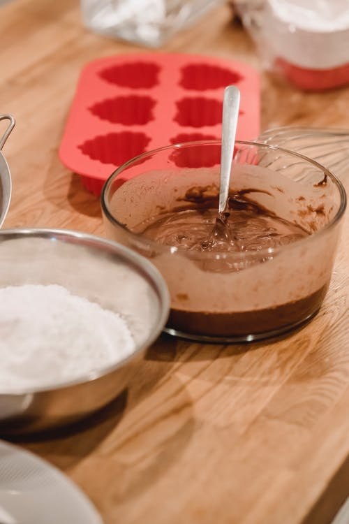 Glass bowl with chocolate batter placed on wooden table with silicone molds and flour in kitchen at home during cooking process