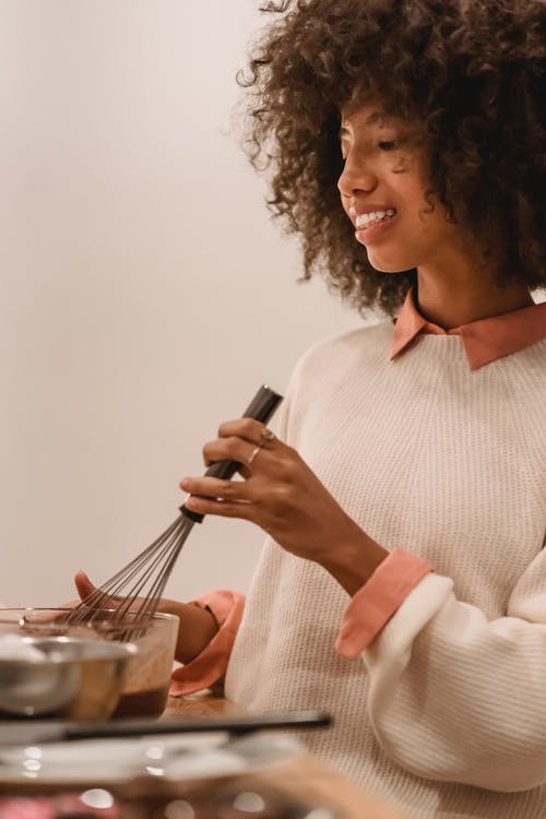 Side view of cheerful African American female with whisk mixing batter at table with dishware while cooking in kitchen