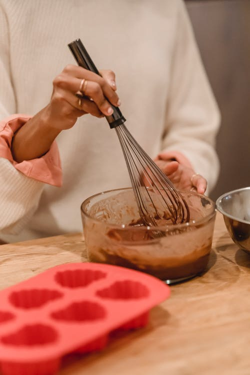 Unrecognizable female cook with whisk mixing batter in bowl while standing at table with silicone mold during cooking in kitchen