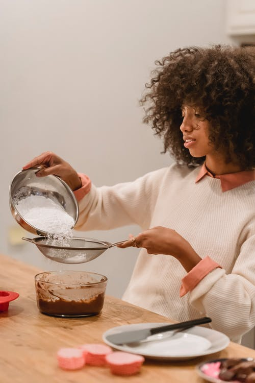 Side view of focused African American female sifting flour into bowl with batter while preparing pastry in kitchen at table