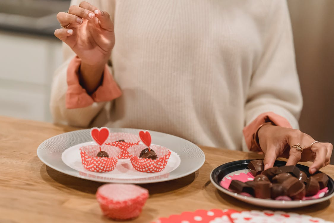 Unrecognizable female serving sweet chocolate candies into molds on plate decorated with red hearts while standing near table in kitchen at home