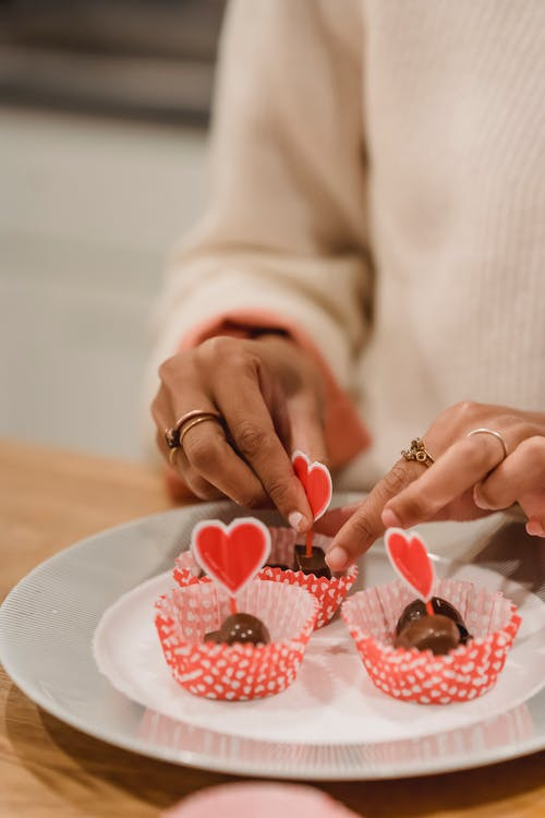 Black woman decorating festive sweets with hearts