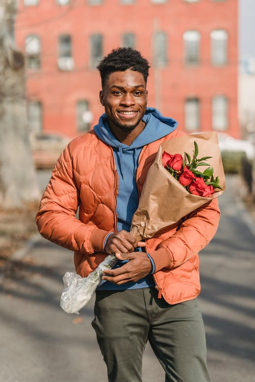 Happy African American male with fresh red roses in paper package on blurred background of town