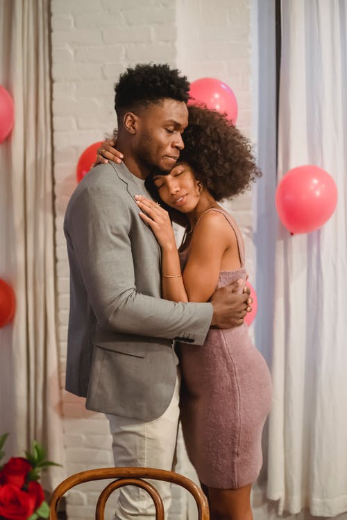 Side view of dreamy young black couple in elegant clothes standing in bright room and cuddling while dancing together with closed eyes near pink balloons on wall