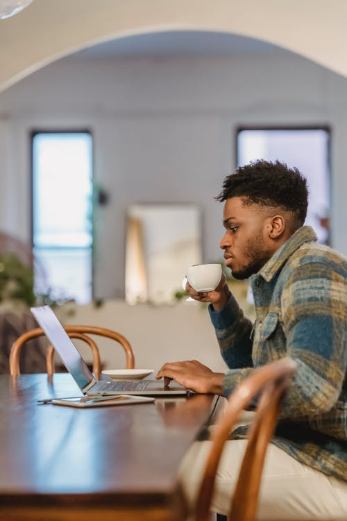 Serious young black man drinking coffee while working remotely on netbook at home