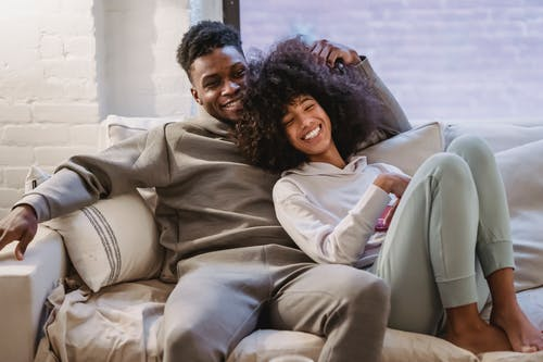 Beloved African American couple cuddling and smiling on couch
