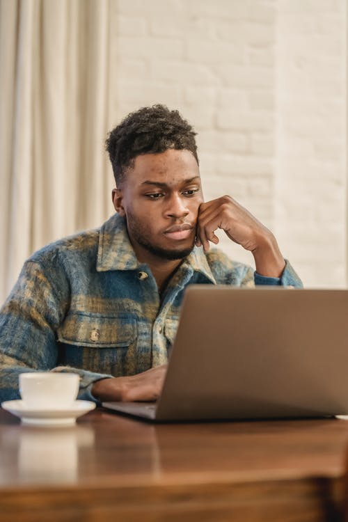 Thoughtful young African American male freelancer in casual clothes sitting at table with hand at chin and working distantly on laptop