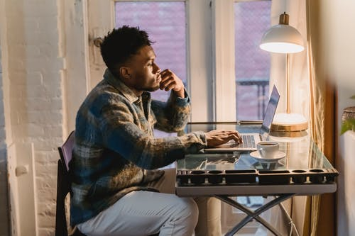 Side view of serious young bearded African American male freelancer in casual clothes typing on laptop sitting at table with cup of coffee during remote work at home