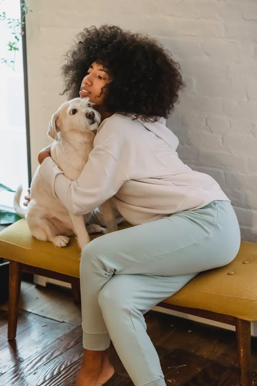 Young African American lady hugging obedient dog at home