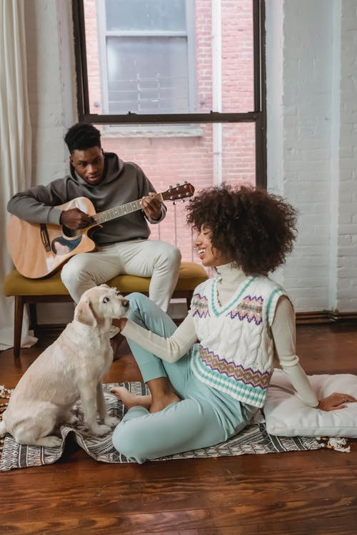 Happy young ethnic woman stroking pet on floor near boyfriend playing guitar