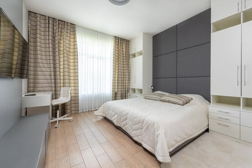 Comfortable bed with beige bedspread and cushions in cozy bedroom with modern furniture