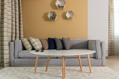 Modern design of living room in pastel colors furnished with big gray couch with cushions placed behind wooden oval table with white surface surrounded by dark yellow walls