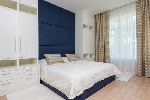 Modern design of comfortable bedroom with wide bed between white wardrobes near big light window and laminate