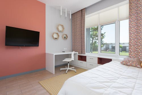 Modern design of comfortable bedroom with light workplace near big window and wide bed in opposite of TV set on coral wall