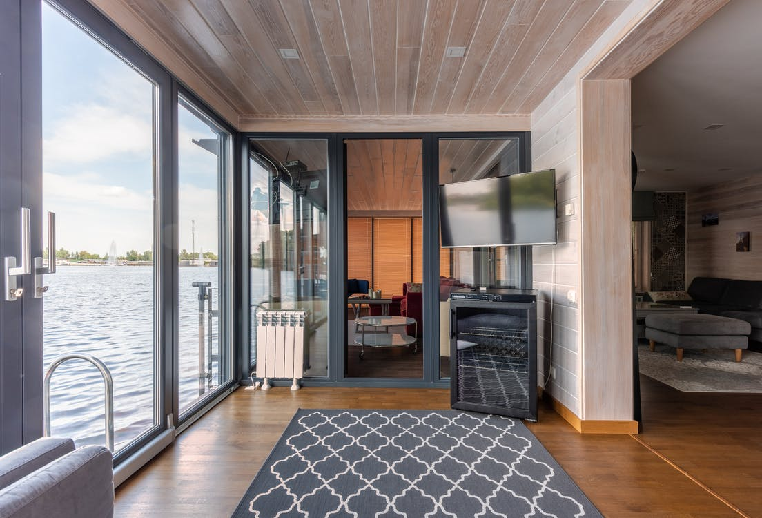Contemporary design of spacious room made from natural materials and colors with overlooking rippled lake surface right behind floor to ceiling windows