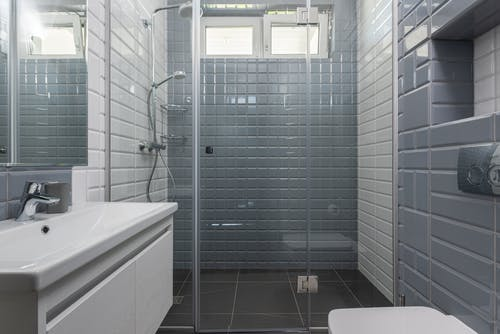 Modern bathroom with shower area behind glass wall