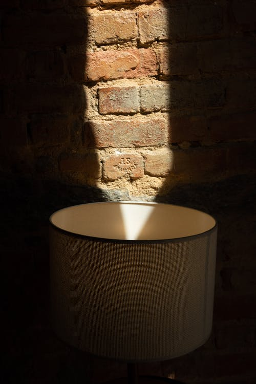 Lampshade near rough brick wall with shadows in sunlight