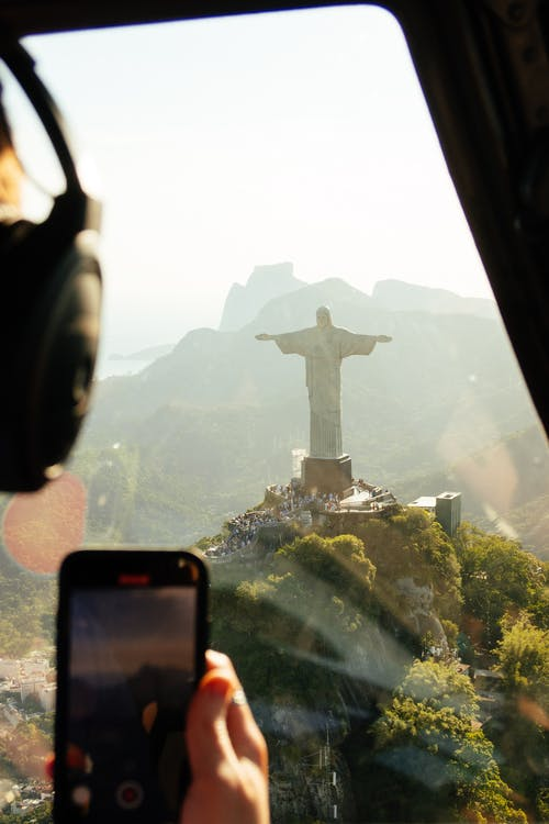 Aerial view of crop unrecognizable pilot in headphones with cellphone in transport against sculpture of Christ Redeemer on mountain in Brazil